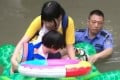 A police officer helps a woman and child steer the inflatable turtle to safety. Photo: Handout