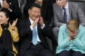 Xi Jinping cracks an unusually large grin as he watches the Germany-China under-12 match with his wife Peng Liyuan and German chancellor Angela Merkel. Photo: EPA