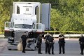 San Antonio police officers investigate the scene where eight people were found dead in a lorry outside a Walmart store. Photo: AP