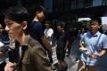 People walking outside an office building in Beijing . Photo: AFP