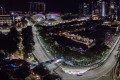 The Formula One Singapore Grand Prix dominates the night sky, with a view of Padang and Turn 9 at Marina Bay Street Circuit.