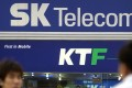 South Koreans cross in front of SK Telecom and KTF 's sign boards in Seoul. Photo: AFP/CHOI JAE-KU