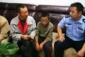 A police officer talks to Miao's father after the youngster was reunited with his family. Photo: Handout