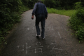 "A villager walks on a path near the nude mansion. ""Take off your clothes freely in your own home,"" reads the writing on the road. Photo: Yonhap"