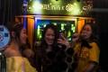 Three women enjoying a sing-song at a karaoke booth in Shenzhen. Photo: EPA
