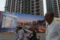 People walk past a billboard advertising a new housing complex outside a construction site in Beijing in May last year. Photo: AFP