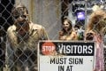 """Zombie characters walk inside a cage at the """"Walking Dead"""" exhibit on the convention show floor during Preview Night of the 2017 Comic-Con International show in July in San Diego. Photo: AP"""