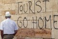 A man walks past a 'Tourists Go Home' graffitti on a wall close to the City Hall in Oviedo, northern Spain. Photo: EPA
