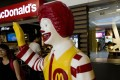 A customer walks past a statue of Ronald McDonald outside a McDonald's restaurant in Beijing. The fast food giant is targeting smaller mainland Chinese cities as part of a five year expansion plan. Photo: AP