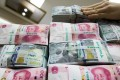 An employee arranges bundles of US one-hundred dollar notes and Chinese one-hundred yuan notes. The dollar rose to its highest in three weeks on US retail sales data and an easing in tensions between the US and North Korea. Photo: Bloomberg