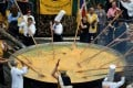 Members of the World Brotherhood of the Huge Omelette stir within a 4 metre diameter frying pan on August 15, 2015 in Malmedy, Belgium, in the traditional event in the town near the German border despite a scandal sweeping Europe involving eggs tainted with the insecticide fipronil. Photo: AFP