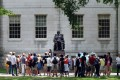 People touring Harvard Yard stop by the John Harvard statue just off Harvard Square in Cambridge, Massachusetts. Photo: AFP