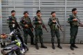 Cambodia police stand at a condo where they arrested dozens of young Chinese men and women. Photo: Reuters