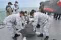 Royal Malaysian Navy personnel move a body bag containing the remains of one of the missing sailors from the USS John S McCain. Photo: Handout