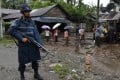 An armed policeman on guard at a displacement camp for the minority Muslim Rohingya in Myanmar's Rakhine State. Picture: AFP