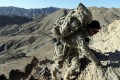 A US soldier climbs a hill with a heavy rucksack in Afghanistan. Photo: Reuters