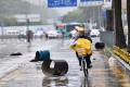 A food delivery worker rides against the rain in Shenzhen, south China, during Typhoon Hato. Photo: Xinhua