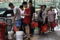 People queue up to collect water from a fire hydrant in Macau on August 24, a day after Typhoon Hato left a trail of destruction, with water supplies badly hit. Photo: AFP