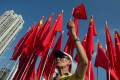 A man holds up a Chinese national flag as he sings the national anthem at an event to celebrate the 65th anniversary of the founding of Communist China at Victoria park in Hong Kong on October 1, 2014. Photo: AFP