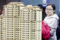 Potential buyers look at models of new residential developments for sale in Beijing. China's big four state-owned banks significantly slowed their lending pace in the first half of this year. Photo: EPA