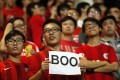 "A Hong Kong fan holds up a sign that reads ""Boo"" while the national anthem was being played during a World Cup qualifier at Mong Kok stadium in Hong Kong on November 17, 2015. AFP PHOTO / ISAAC LAWRENCE"