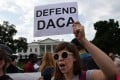 Protesters hold up signs during a rally supporting Deferred Action for Childhood Arrivals, or DACA, outside the White House. Photo: TNS