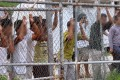Asylum seekers look through a fence at the Manus Island detention centre in Papua New Guinea. Photo: Reuters