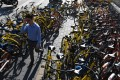 A man walks past shared bicycles on a Beijing sidewalk in Beijing on August 3. China on August 3 issued national guidelines governing bike-sharing operations to nurture a new industry credited with spurring a transport revolution while addressing mounting complaints over an accumulation of millions of bikes on city streets. The yellow bicycles are operated by Ofo, while the orange units are operated by Mobike. Photo: AFP