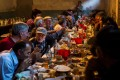 Family and friends gather at a supra, or feast table, to celebrate the first birthday of a family's first child. Photo: Alamy