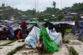 A Rohingya refugee woman sits next to a makeshift shelter in a camp in the Bangladeshi locality of Ukhia. Photo: AFP