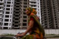 An Indian cyclist rides past incomplete residential flats in Greater Noida, southeast of New Delhi. Real estate accounts for about US$19.5 billion of stressed loans in India. Photo: AFP