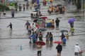 Residents in Manila wade through floodwater after a tropical depression caused mass flooding in the city and nearby areas. Photo: AP