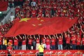 Fans hold up the flag of China as the national anthem plays before the start of the Fifa World Cup 2018 qualification match against Qatar, in Doha on September 5. Photo: AFP