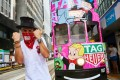 American street graffiti artist, who calls himself Alec Monopoly, beside his latest 'canvas' – a Hong Kong tram in Central.