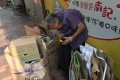 An 89-year-old woman collects used cardboard in Causeway Bay. Photo: Denise Tsang