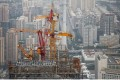 Cranes are seen on top of an under-construction skyscraper in Beijing last month. All major public projects in the city will be banned for four months as the government seeks to improve air quality. Photo: Reuters