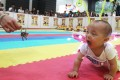 Baby Leung Yi-shun takes part in a crawling contest at the 2013 International Baby Expo at the Hong Kong Convention and Exhibition Centre. Photo: SCMP Picture