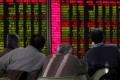 A file picture of investors monitoring stock prices at a brokerage in Beijing. Photo: Reuters