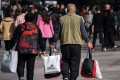 A couple carry bags along the main shopping street in Shanghai last November. More market rather than less is key to sustaining China's economic growth in the long term. Photo: AFP