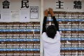 A student union member removes Hong Kong independence posters to make space for other students to display notices, at Chinese University on September 7. Photo: AFP