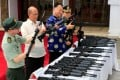Philippine Defence Secretary Delfin Lorenzana (second from left) and Chinese ambassador the Philippines Zhao Jianhua (second from right) inspect automatic rifles during a handover of military supplies at Camp Aguinaldo in Quezon city. Photo: Reuters
