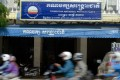 Motorbikes speed past the headquarters of the Cambodia National Rescue Party in Phnom Penh, Photo: AFP
