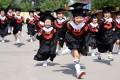 Children in gowns and mortarboards run with smiles during their kindergarten graduation ceremony in a kindergarten in Handan, Hebei province, China. Photo: REUTERS