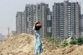 A village woman carries potted water as she walks in front of a backdrop of under construction high rise housing in Gurgaon, a suburb south of New Delh. Photo: AP
