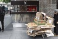 An elderly woman collecting scrap cardboard boxes to resell goes about her work outside the Louis Vuitton store in Central. Photo: EPA