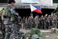 The Philippine flag is held by a soldier after government troops cleared Marawi of militants. Photo: Reuters