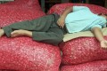 An exhausted onion trader catches forty winks on top of piles of his merchandise. Photo: Reuters