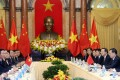 Chinese President Xi Jinping (right) listens as Vietnamese President Tran Dai Quang speaks at the Presidential Palace in Hanoi on Monday. Photo: Reuters