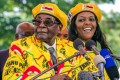 Zimbabwe's President Robert Mugabe (left) is likely facing the end of his iron-fisted reign, with a military takeover of the southern African nation on Wednesday. Earlier in November, he dismissed his Vice-President, a move that many saw as paving the way for his wife Grace (right) to run the country when he dies or steps down. Photo: AFP