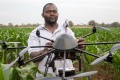 A technician holds a drone used to scout a plot of a heat-tolerant hybrid corn growing at the Chiredzi Research Station, in Zimbabwe, in October 2016. Africa's largest employer is agriculture. In China, agriculture was modernised by granting more autonomy to farmers, alongside state investment in food-processing facilities. Photo: AFP